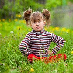 Lovely little five-year girl sitting in grass.