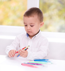 Little boy is writing using a pen