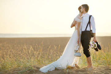 Bride and groom on a beach at sunset