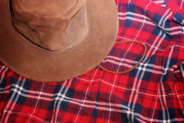Brown cowboy leather hat on red tartan shirt background