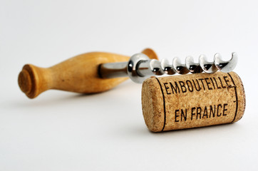 vintage corkscrew and wine cork with inscription embouteille en