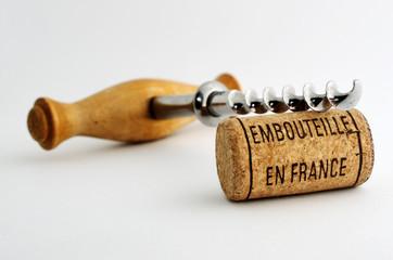 vintage corkscrew and wine cork with inscription embouteille en