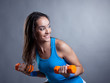 Merry young woman exercising with dumbbells
