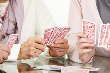 Hände von Senioren beim Karten spielen