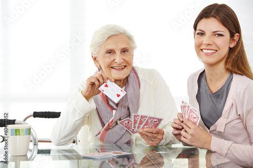Leinwanddruck Bild Junge Frau spielt Karten mit Seniorin