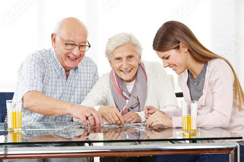 Paar Senioren löst Puzzle mit Enkeltochter