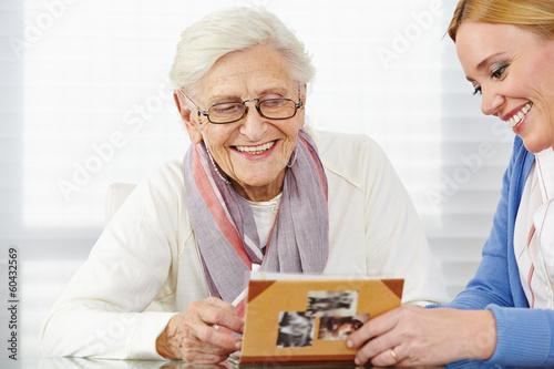 Seniorin schaut Fotos an mit Tochter - 60432569