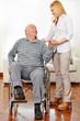 Frau hilft Senioren im Rollstuhl