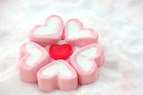 heart shape candy around by marshmallows on snow