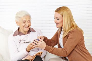 Frau hilft Seniorin mit ihrem Smartphone