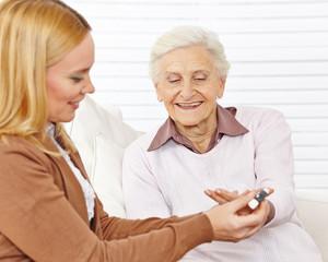 Frau macht Blutzuckermessung bei Senioren