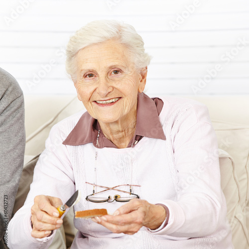 Alte Frau schmiert Brot zum Frühstück