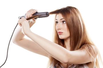 redheaded girl straightens the hair using a hair straightener