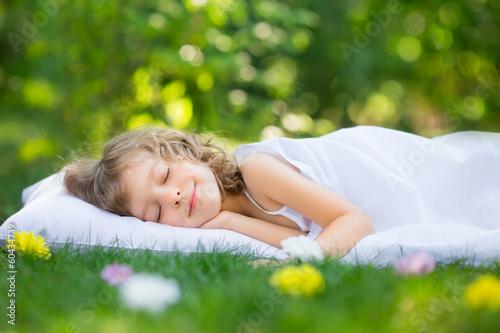 Kid sleeping in spring garden - 60434739