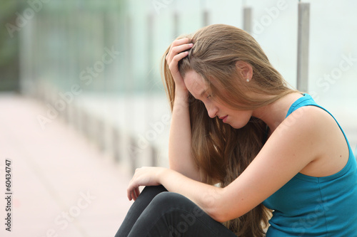 Teenager girl sitting outdoor depressed
