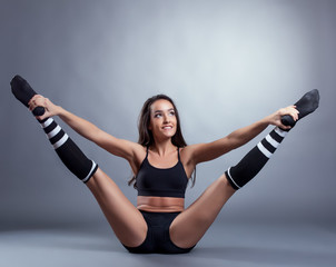Seductive brunette doing stretching exercises