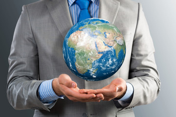 businessman holds up a planet Earth