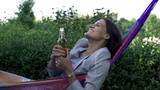 Happy businesswoman drinking beer in hammock, slow motion shot a