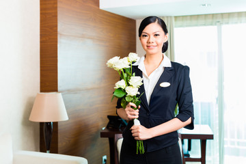 Asian Chinese hotel manager welcomes arriving VIP guests