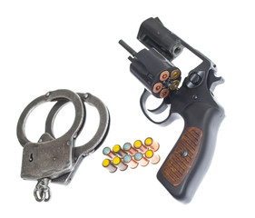 Handgun with handcuffs and bullets isolated on white