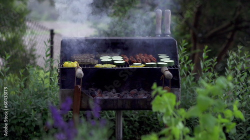 Grilling food on the BBQ in the garden, slow motion shot at 240f