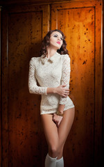 Beautiful brunette woman in white sensual lace outfit posing