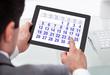 Businessman Looking At Calendar On Digital Tablet