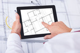 Male Architect Analyzing Blueprint Over Digital Tablet