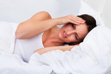 Upset woman lying on bed