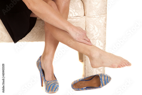 Woman skirt shoe off rub leg toes out