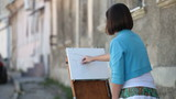 Young girl artist drawing town street