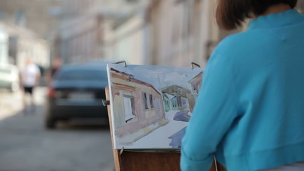 Girl artist painting picture in watercolor on the street