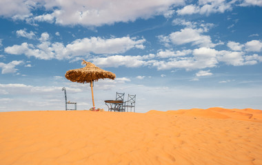 Sun umbrella and chairs in desert