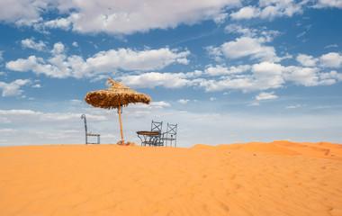 Sun umbrella and chairs in desert