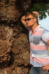 Парень стоит рядом с древнем деревом.