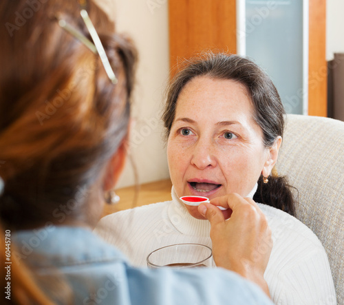 woman giving the cough syrup to mature mother