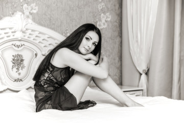 Attractive brunette woman on bed in black and white