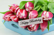 Happy birthday with pink tulips on blue tray