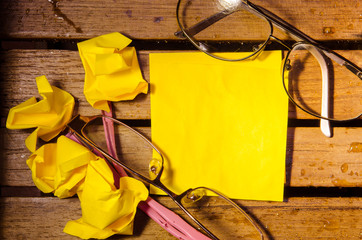 yellow blank paper with crumpled paper with two glasses