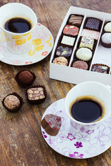 Assorted chocolate candies and two cups of coffee on a wooden ta