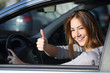 Leinwanddruck Bild - Happy woman inside a car gesturing thumb up