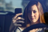 Front view of a woman driving a car and typing on a smart phone
