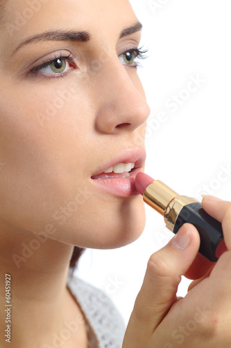 Close up of a beautiful woman applying a lipstick on lips