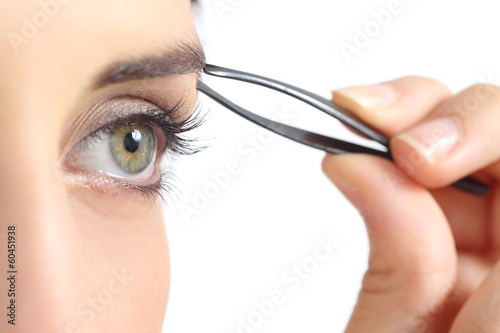 Close up of a woman eye and a hand plucking eyebrows
