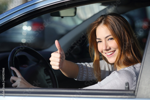 Leinwanddruck Bild Happy woman inside a car gesturing thumb up