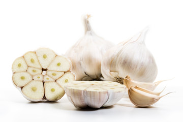 Three bulbs of fresh garlic with several cloves.