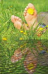 zwei Füße im Gras über spiegelndem Wasser