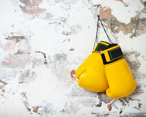 Pair of yellow boxing gloves hanging