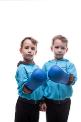 Two serious twins posing in boxing gloves