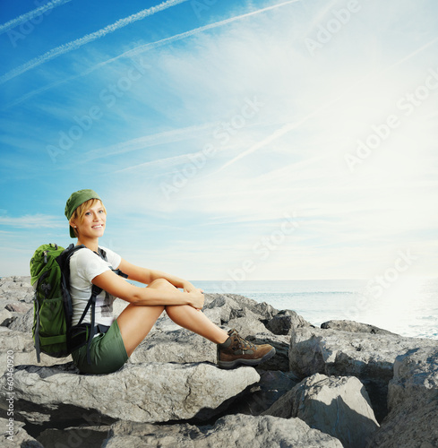 young traveler woman sitting on a rock near water